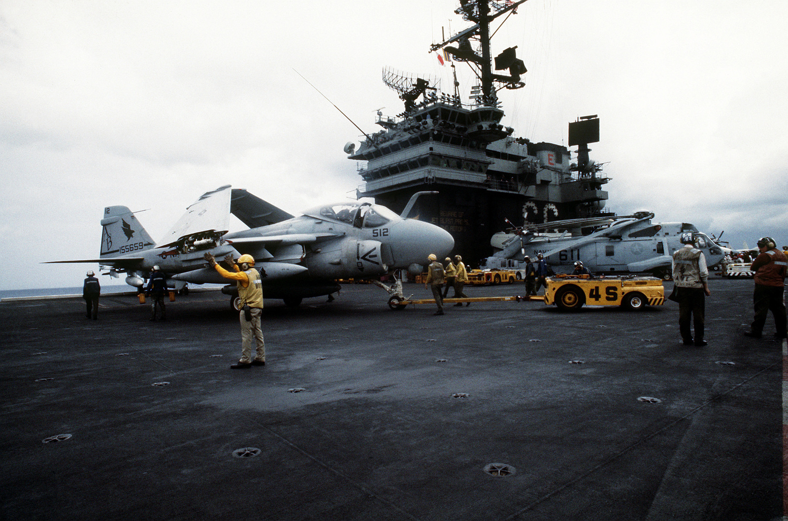 Flight deck crewmen use an MD-3A tow tractor to position an A-6E Intruder aircraft on the flight deck of the aircraft carrier USS AMERICA (CV-66) during the joint service exercise Ocean Venture '93
