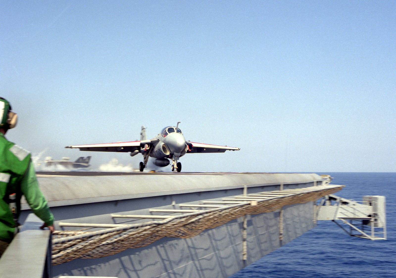 Flight deck crewmen watch from the deck edge as an A-6E Intruder aircraft is launched from the nuclear-powered aircraft carrier USS THEODORE ROOSEVELT (CVN-71) during Operation Deny Flight