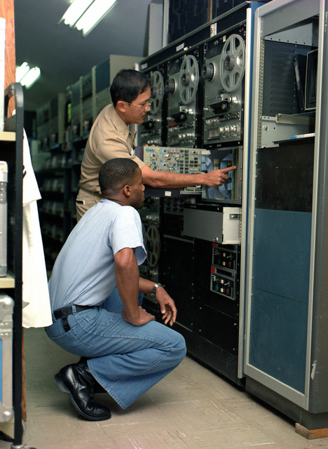 Manuel S. Patio, chief engineer, and Interior Communication Electrician 2nd Class Joe L. Campbell examine equipment at the Navy Broadcasting Service Detachment, Diego Garcia, radio station