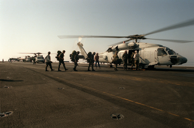 Members of the Special Purpose Marine Air Ground Task Force (SPMAGTF) board a Helicopter Anti-submarine Squadron 3 (HS-3) SH-60F Sea Hawk on the flight deck of the nuclear-powered aircraft carrier USS THEODORE ROOSEVELT (CVN-71). The Marines are going to participate in a training exercise in Italy. The ROOSEVELT is operating in the Adriatic in support of Operation Deny Flight