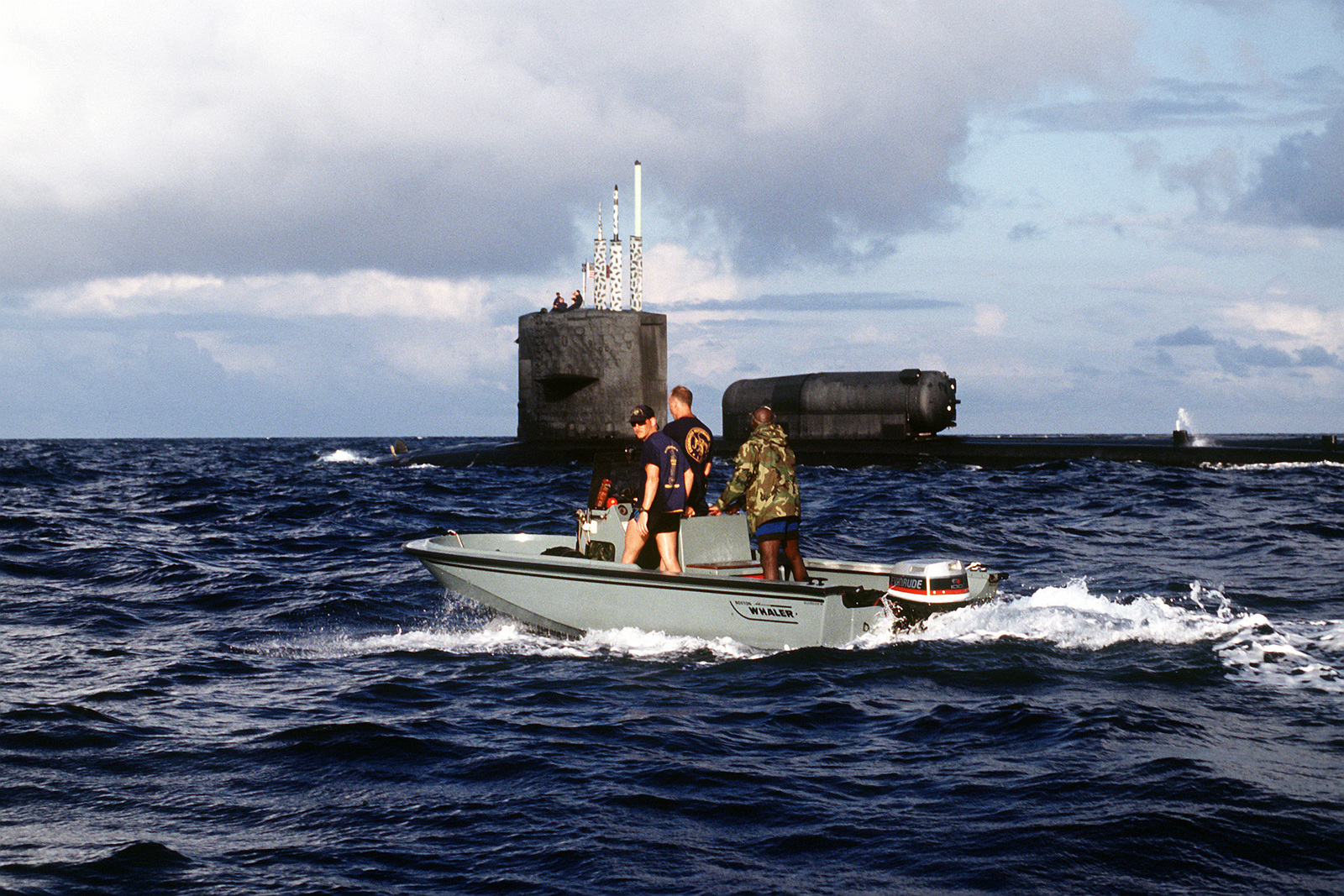 Navy divers approach the nuclear-powered attack submarine USS