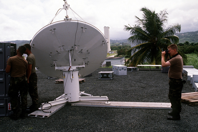 STAFF SGT. Paul Caron of the 1ST Combat Camera Squadron photographs members of the Joint Combat Camera Satellite Team as they assemble a satellite transmitter dish on the roof of the Fleet Imaging Command photo lab. The transmitter will be used to send video footage of the joint service Exercise Ocean Venture '93 to the Joint Combat Camera at the Pentagon