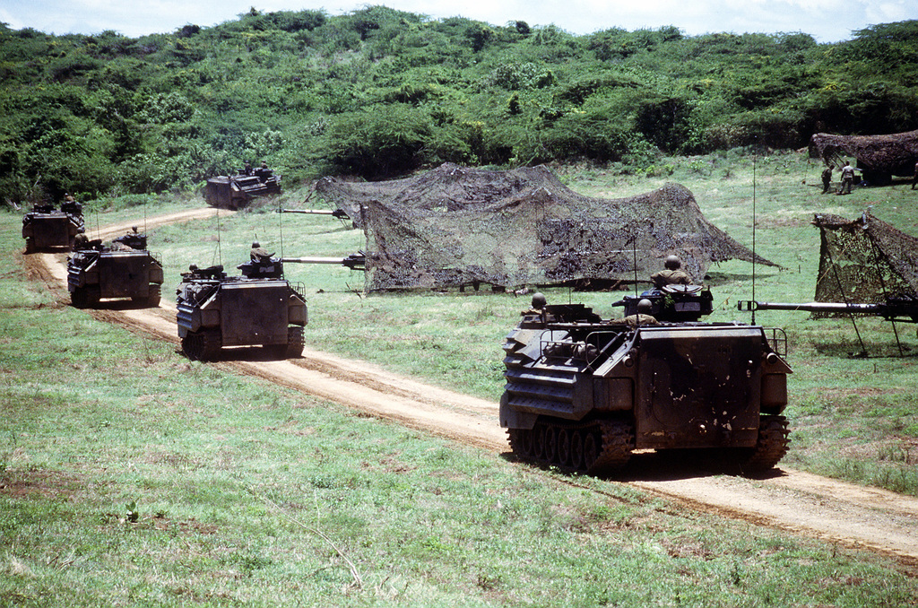 A convoy of AAVP-7A1 assault amphibian vehicles passes the camouflaged M-198 155mm howitzers of Btry. R, 5th Bn., 10th Marine Regt., during the joint service exercise Ocean Venture '93