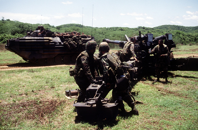 Members of Btry. R, 5th Bn., 10th Marine Regt., position the trails of an M-198 155mm howitzer while setting up an artillery position during the joint service exercise Ocean Venture '93. An AAVP-7A1 assault amphibian vehicle is passing by in the background