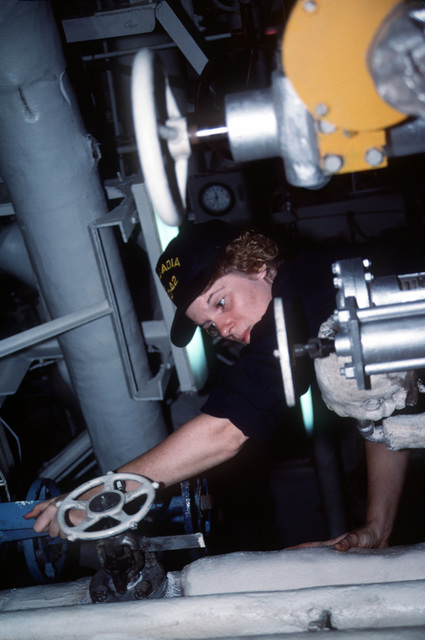 Boilerman Technician/Fireman Rebecca Powers turns a valve to maintain the discharge pressure of the No. 2 main feed pump aboard the destroyer tender USS ACADIA (AD-42)