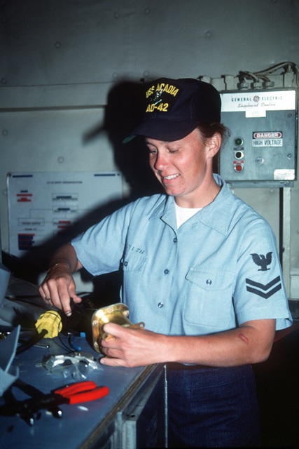Electrician's Mate 2nd Class Lisa Smith checks a power receptacle aboard the destroyer tender USS ACADIA (AD-42)