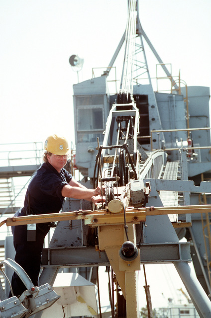 Equipment Operator 1ST Class Michelle Stiff checks the switches on a crane boom aboard the medium auxiliary floating dry dock STEADFAST (AFDM-14)