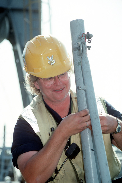 Equipment Operator 1ST Class Michelle Stiff repairs a stanchion aboard the medium auxiliary floating dry dock STEADFAST (AFDM-14)