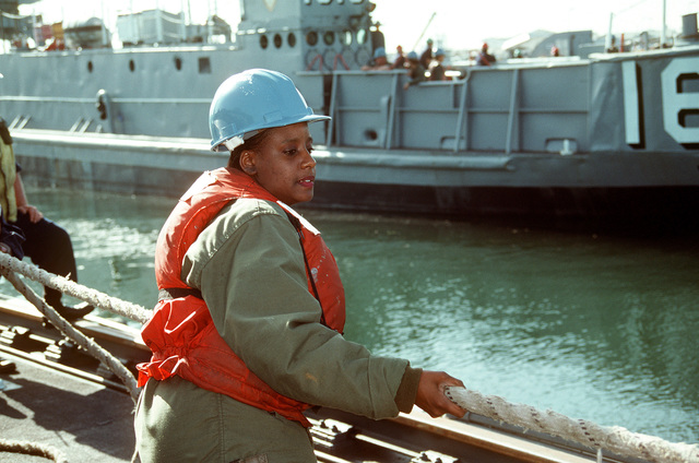 Standing aboard the medium auxiliary floating dry dock STEADFAST (AFDM-14), SEAMAN Recruit Tracie Wallace works as a line handler as utility landing craft LCU 1616, background, is undocked