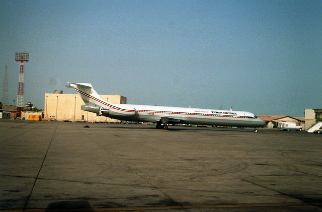 A right side view of a Kuwait Air Force MD-80 series aircraft parked on a flight line