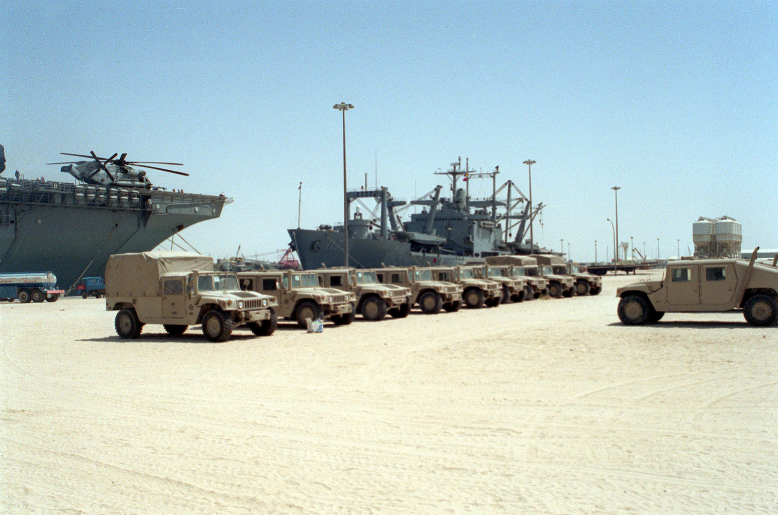 Various types of M-998 high-mobility multipurpose wheeled vehicles are parked on the dock at Jebel Ali. The amphibious cargo ship USS EL PASO (LEA-117) and the bow of the amphibious assault ship USS WASP (LHD-1) are in the background