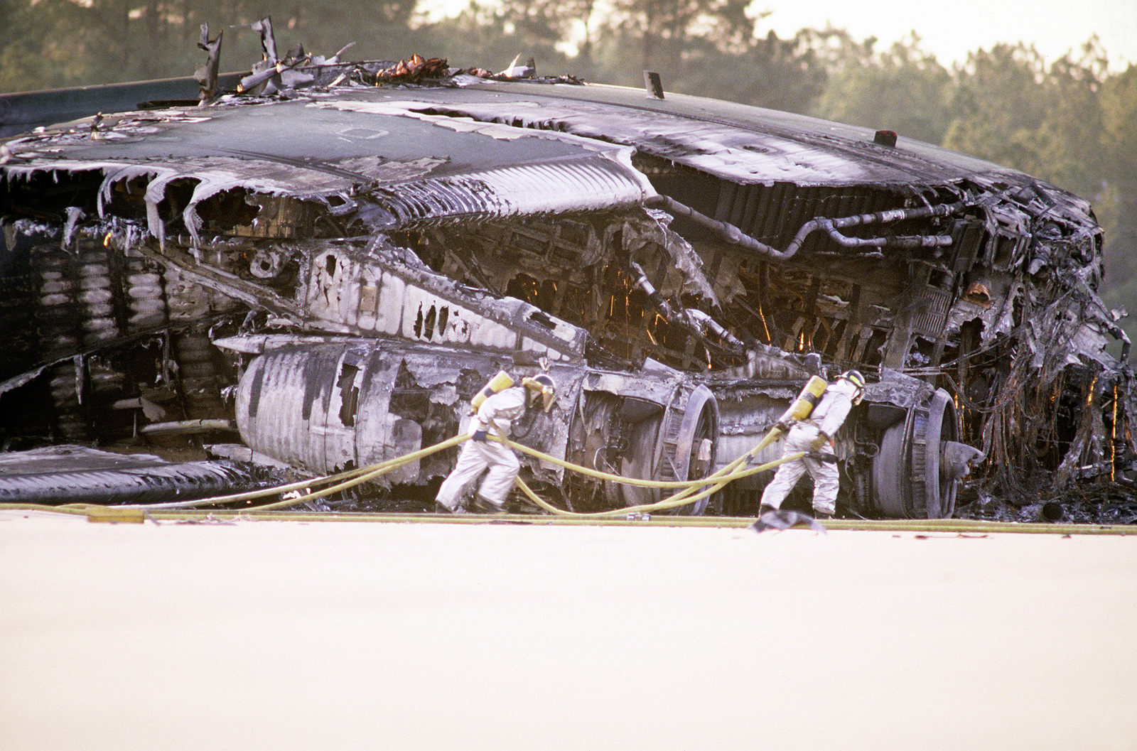 Pope Air Force Base firefighters drag fire hoses in front of a C-141 that was destroyed when an F-16 crashed into it, after a mid-air collision with a C-130 over the base. Exact Date Shot Unknown . Published in AIRMAN Magazine, May 1994