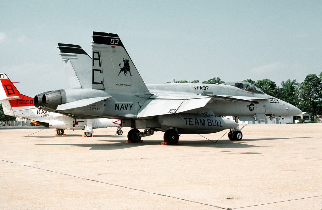 A right rear view of an F/A-18C Hornet aircraft assigned to Strike Fighter Squadron 37 (VFA-37) of Carrier Wing (CVW-3) parked on the flight line. Behind the F/A-18C is an T-2C Buckeye trainer aircraft of Training Squadron 23 (VT-23)