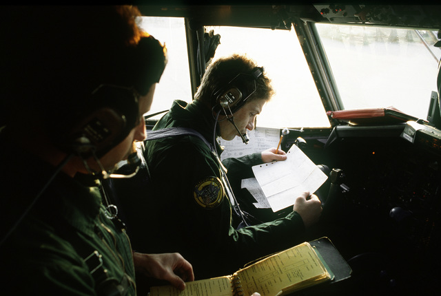 MAJ Pascal Kolfenter (background) and CPT Phil Grollemund, French Air Force C-160 Transall pilot and co-pilot are assigned to Anjou Tactical Squadron, 64th Wing, Eureux Air Base, France and deployed to Rhein Main Air Base, prepares for a TRIADS MRE drop into Srebernica, Bosnia