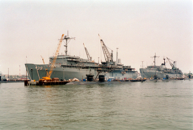 A port bow view of the submarine tenders USS EMORY S. LAND (AS-39) and the USS HUNLEY (AS-31) moored to the destroyer and submarine piers at Norfolk Naval Base. Several Los Angeles class attack submarines are tied to the pier in the foreground