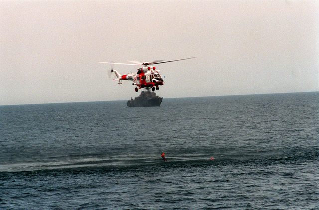 A Polish PZL Swidnik W-3 Sokol helicopter hoists a swimmer out of the water while conducting a search and rescue demonstration during exercise BALTOPS '93. The guided missile frigate USS DOYLE (DDG-39) is in the background. For the first time in the 22-year history of BALTOPS, the Eastern European countries of Estonia, Latvia, Lithuania, Poland and Russia were invited to participate in the non-military phases of the exercise