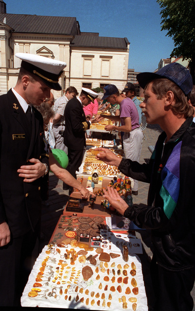 A U.S. Naval Academy midshipman examine a street vendor's merchandise while on liberty from the guided missile frigate USS DOYLE (FFG-39) during exercise BALTOPS '93. For the first time in the 22-year history of BALTOPS, the Eastern European countries of Estonia, Latvia, Lithuania, Poland and Russia were invited to participate in the non-military phases of the exercise. DEYO is serving as flagship for the exercise commander