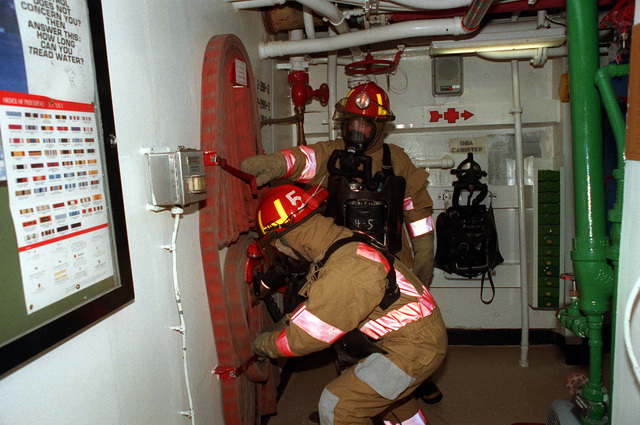 Crewmen wearing oxygen breathing apparatus remove a fire hose from a wall rack while participating in a damage control drill aboard the guided missile frigate USS DOYLE (FFG-39) during exercise BALTOPS '93