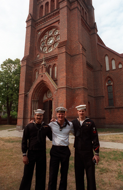 Damage Controlman 2nd Class Ronald J. Mosholder and Machinery Repairman 2nd Class Anthony Simpson pose for a photo with a German sailor in front of the Vytautas Catholic Church while on liberty from the guided missile frigate USS DOYLE (FFG-39) during exercise BALTOPS '93. For the first time in the 22-year history of BALTOPS, the Eastern European countries of Estonia, Latvia, Lithuania, Poland and Russia were invited to participate in the non-military phases of the exercise. DEYO is serving as flagship for the exercise commander