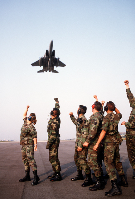 Five maintenance personnel from the 53rd Fighter Squadron, Bitburg Air Base, Germany, gives a fist salute to an F-15 Eagle flying over them. The 53rd Fighter Squadron is enforcing the No-Fly Zone over Bosnia