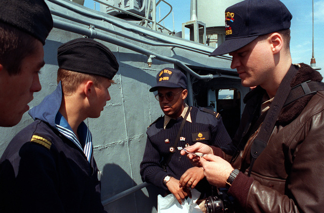 Midshipman 1ST Class Michael Nelms, center, serves as an interpreter between a crew member of the USS DEYO (DD-989) and Russian sailors who are visiting the destroyer during exercise BALTOPS '93. For the first time in the 22-year history of BALTOPS, the Eastern European countries of Estonia, Latvia, Lithuania, Poland and Russia were invited to participate in the non-military phases of the exercise