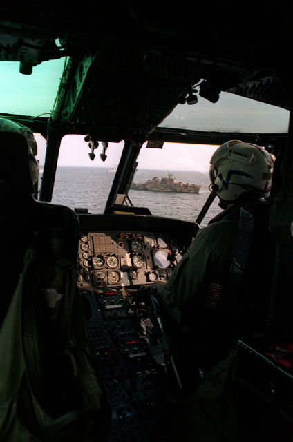 The pilot and copilot of an SH-3 Sea King fly their helicopter toward a formation of ships during Exercise Baltops '93
