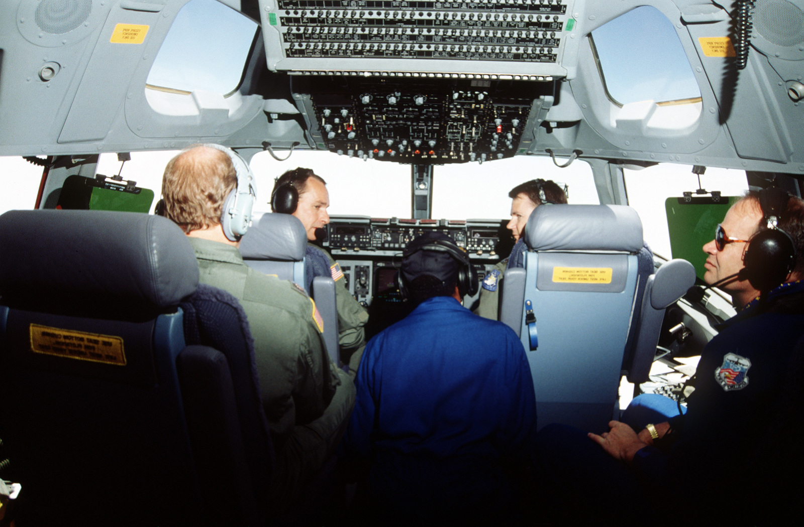 Interior of the C-17, the first one to be delivered to the Air Force, cockpit enroute from McDonnell Douglas plant in Long Beach, CA. Aircraft Commander, LTC Giles Gentry, 437th Airlift Wing (left) at the controls and co-pilot, MAJ Joseph B. Niemeyer, 17th Airlift Squadron on right. On far left is second co-pilot, MAJ Paul Skyes, 317th Airlift Squadron, on far right is Mr. David Swain, McDonnell Douglas Vice President in charge of C-17 production and in center is McDonnell Douglas avionics technician, Mr. Arlanders Ewing