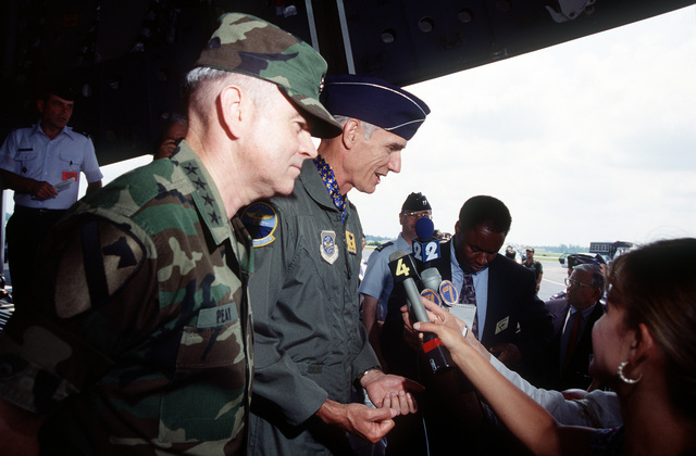 Air Force CHIEF of STAFF, GEN Merrill McPeak and U.S. Army Vice CHIEF of STAFF GEN Peay talk with the press from the C-17's cargo bay after turnover ceremonies for the first C-17 Globemaster III delivered to the Air Force