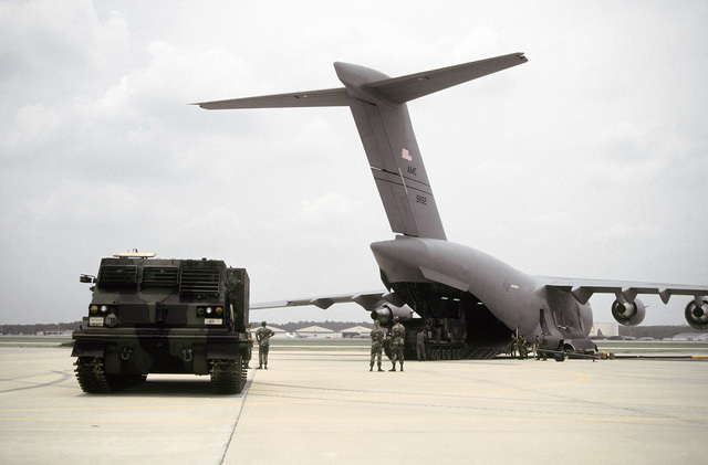 "MSGT Dave Saucier, Loadmaster, 1275th Test & Evaluation Squadron, Edwards AFB, CA directs the loading of one 82nd Airborne Mobile Launch Rocket System (MLRS) onto the ""Spirit of Charleston."" Another MLRS stands by to load onto the first C-17 Globemaster III delivered to the Air Force"