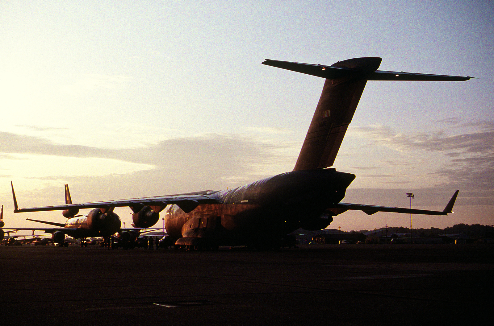 The first C-17 Globemaster III delivered to the Air Force's 437th Airlift Wing, on 14 Jun 93, sits on the ramp, silhouetted by the rising sun