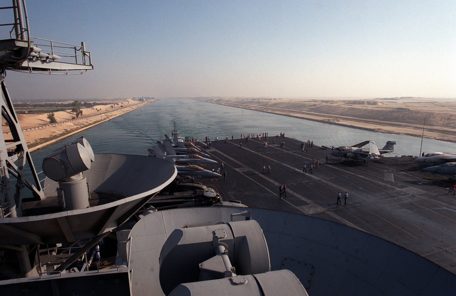 A crew member watches from the aft flight deck as the nuclear-powered aircraft carrier USS THEODORE ROOSEVELT (CVN-71) transits the Suez Canal en route to the Red Sea
