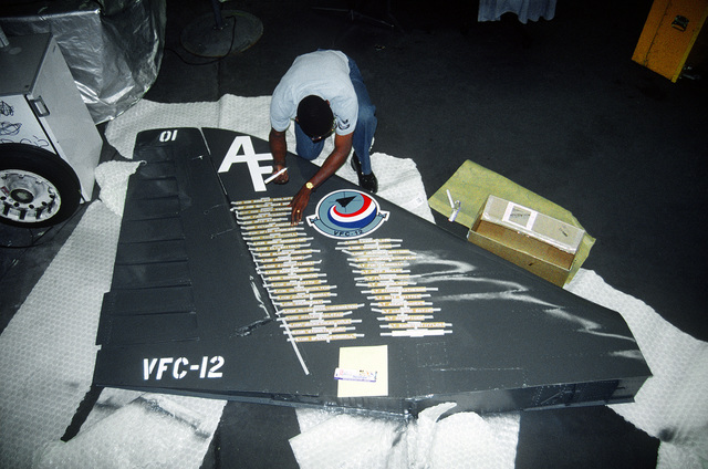 An airman places pilot names onto the tail of an A-4 Skyhawk aircraft of Navy Composite Squadron 12 (VFC-12). The tail is being prepared for display in commemoration of all of the Skyhawk aircraft, which are scheduled for retirement from service on October 1