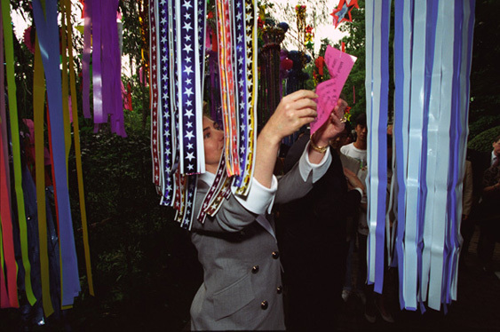 Photograph of First Lady Hillary Rodham Clinton Reading a Message Attached to Hanging Streamers in Tokyo, Japan