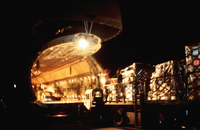 A 40-K loader is used for night off-loading of a C-5 Galaxy cargo aircraft. Due to heavy commercial air traffic during the day, the Tactical Airlift Control Squadron started night operations to support this United Nations peacekeeping operation