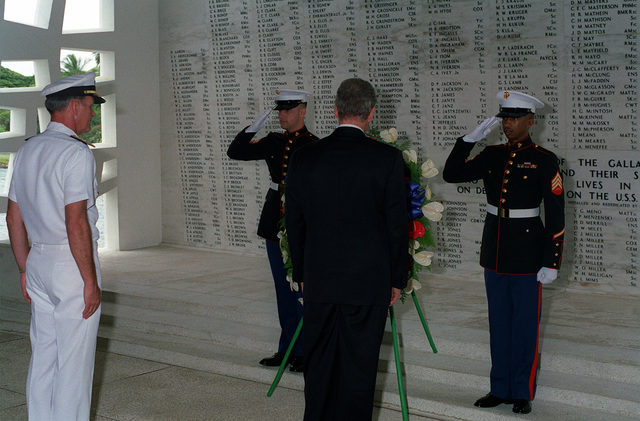 A Marine honor guard salutes as President William Jefferson Clinton places a wreath in the chamber of fallen heroes aboard the ARIZONA (BB-39) Memorial. Adm. Charles R. Larson, commander-in-chief, U.S. Pacific Fleet, stands by at left. Clinton is in Hawaii to tour area military installations