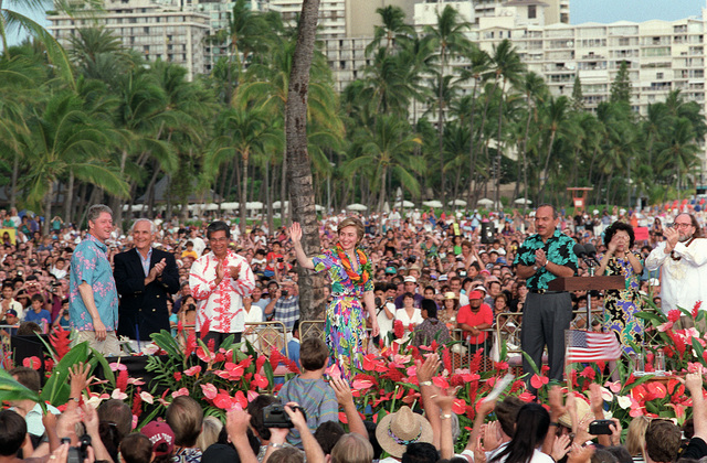 Hillary Rodham Clinton waves to the crowd gathered on Wakiki Beach to hear President William Jefferson Clinton speak. Hawaiian Governor John Waihee stands to the right of Mrs. Clinton. The Clintons are in Hawaii to tour area military installations