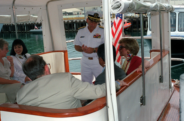 Members of the presidential party, including Hillary Rodham Clinton, right, and Rear Adm. (lower half) William A. Retz are transported by admiral's barge to the ARIZONA (BB-39) Memorial. The Clintons are in Hawaii to tour area military installations