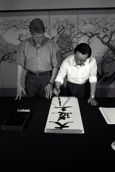 Photograph of President William J. Clinton Watching South Korean President Kim Young-sam Prepare a Calligraphy Scroll