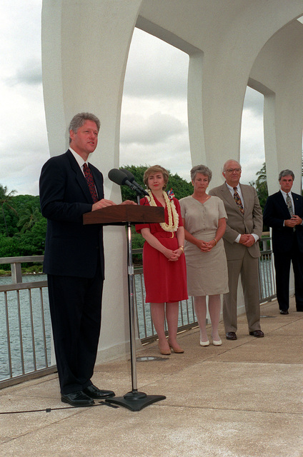 President William Jefferson Clinton speaks during a ceremony aboard the ARIZONA (BB-39) Memorial as Adm. Charles R. Larson, commander-in-chief, U.S. Pacific Fleet, Hillary Rodham Clinton, Secretary of Defense Les Aspin and Mrs. Aspin stand by. Clinton is in Hawaii to tour area military installations