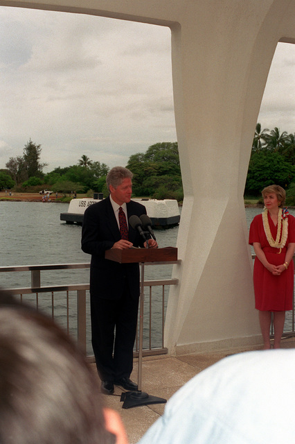 President William Jefferson Clinton speaks during a ceremony aboard the ARIZONA (BB-39) Memorial as Hillary Rodham Clinton stands by. The Clintons are in Hawaii to tour area military installations