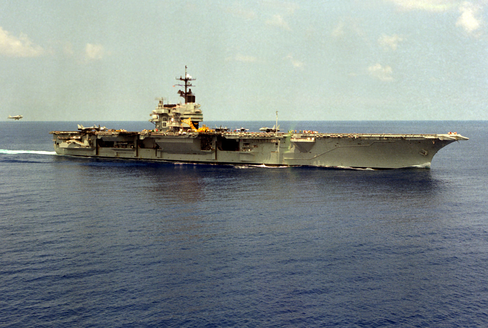 A starboard view of the aircraft carrier USS SARATOGA (CV-60) underway as an A-6E Intruder aircraft approaches for a landing