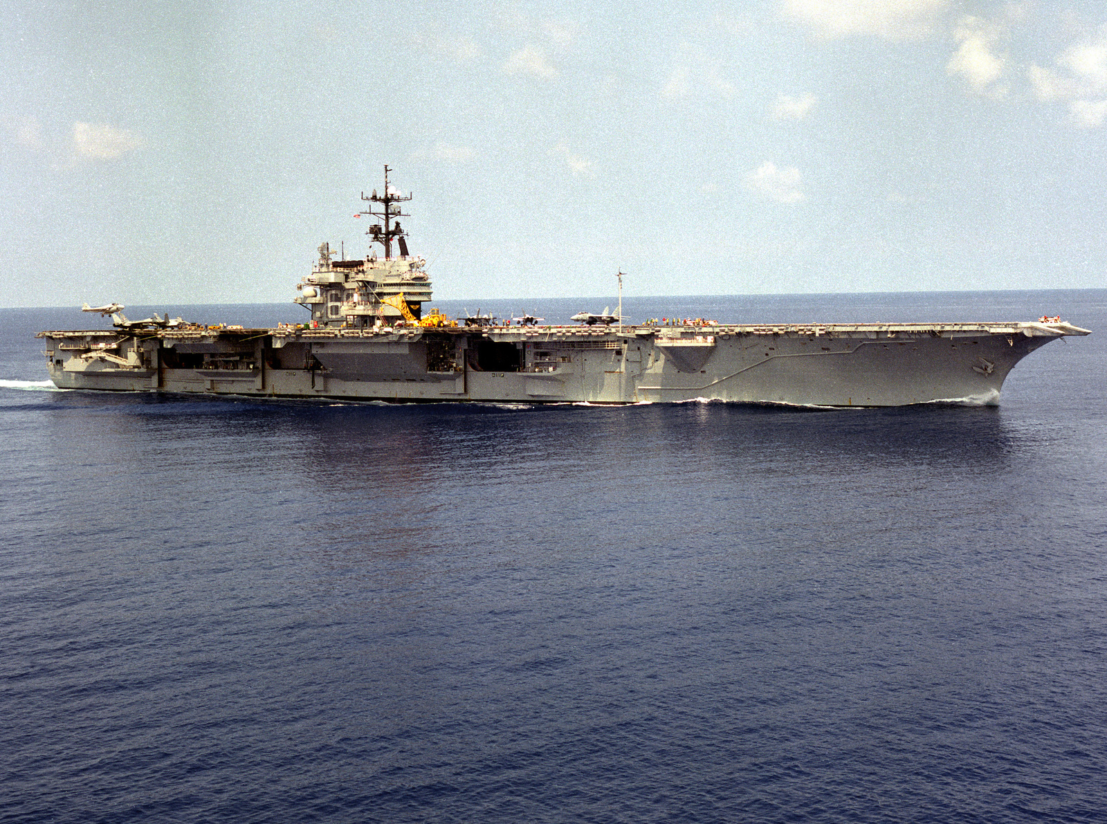 A starboard view of the aircraft carrier USS SARATOGA (CV-60) underway as an A-6E Intruder aircraft prepares to land on the flight deck