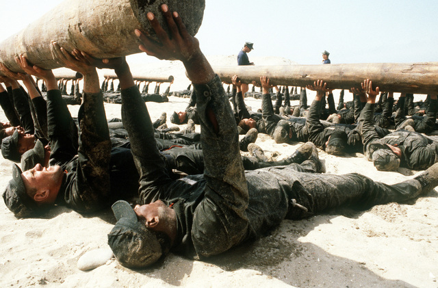 A group of Basic Underwater Demolition/SEAL (BUD/S) students manhandle logs to build both teamwork and body conditioning at the Naval Special Warfare School during Fourth phase training