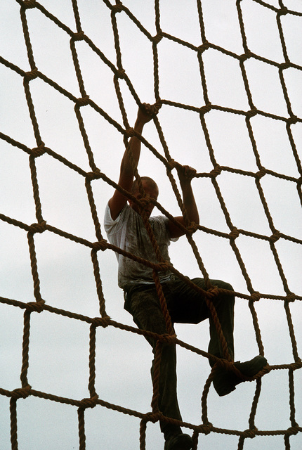 A student at the Naval Special Warfare Center Basic Underwater Demolition/SEAL (BUD/S) training course climbs up a rope obstacle. The obstacle course takes BUD/S students over and under more than a dozen challenges