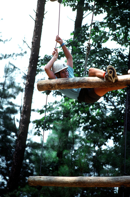 A young Boy Scout gives his all as he pulls himself to the top of an obstacle in the confidence course challenge being held at the army base during the 1993 National Scout Jamboree. Sailors from various commands shared their expertise with more than 35,000 Scouts from the United States and 64 other nations