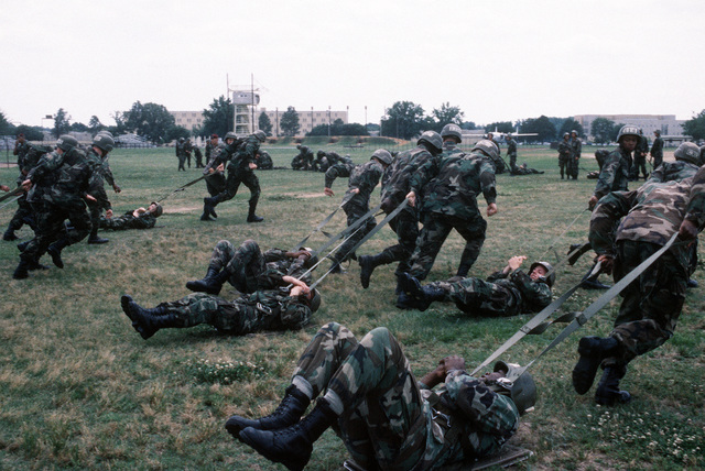 """During """"the second week of training, known as tower week, at the Army Airborne School, Basic Underwater Demolition/SEAL (BUD/S) students practice aircraft exit and how to recover immediately after a landing. Here students pull one another to get the feel of being caught by a cross wind upon landing"""