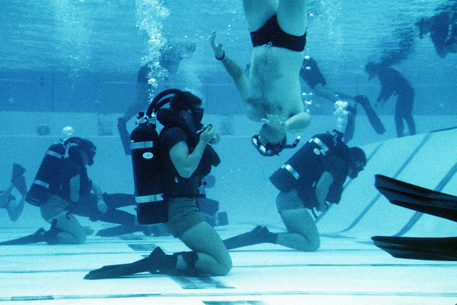 Second phase instructors keep a close eye on Basic Underwater Demolition/SEAL (BUD/S) in the combat training tank. The (BUD/S) are learning to exchange scuba gear while submerged