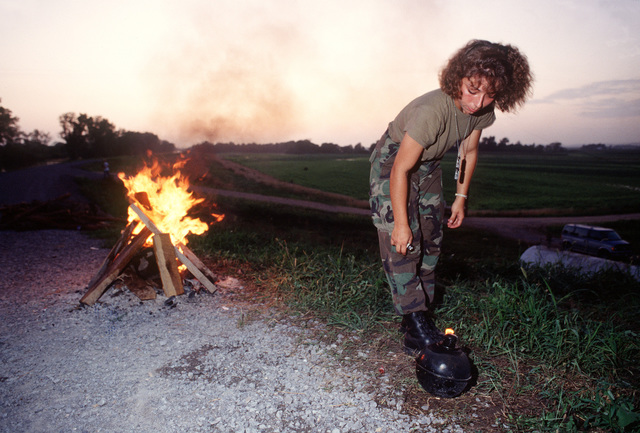 SENIOR AIRMAN Theresa Sronce from the 182nd Fighter Group, Peoria, Illinois lights a smudge pot to keep the mosquitoes away on the Mississippi River