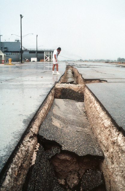 Peter Wagner, a local journalist, looks at a large split in the pavement caused by an earthquake that struck the area on August 8th