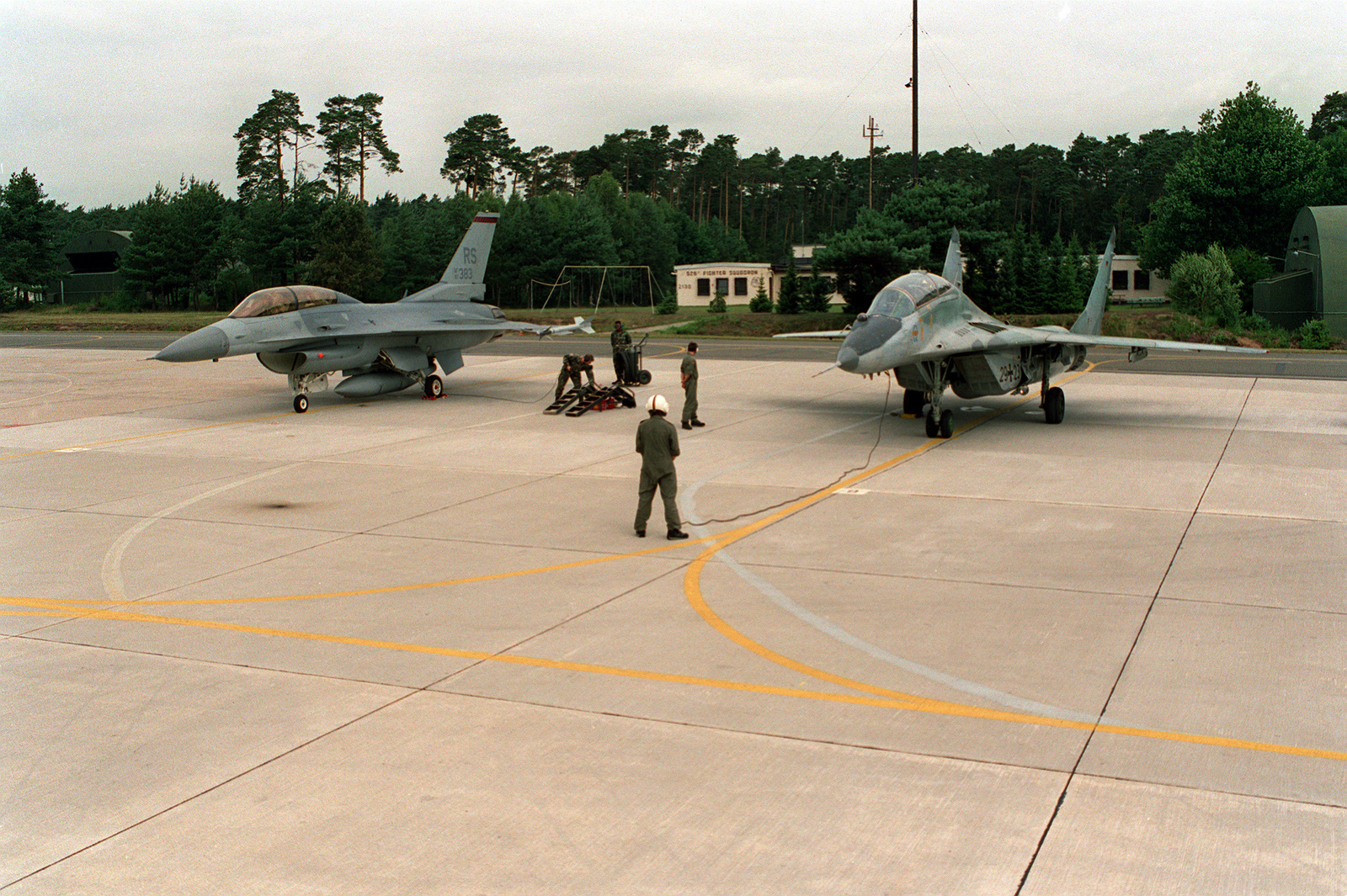 German MIG-29 (right) next to U.S. Air Force F-16 parked on the flightline. Following their MIG-29 flight, MAJ. Gassner and GEN. Oaks reversed roles and embarked on a flight in the F-16. Since the end of the Cold War, armed forces from the east and west are meeting to further understand and strengthen friendships. Such a visit occurred when a MIG-29 from the former East Germany landed and hosted a flight for GEN. Oaks. GEN. Oaks returned the favor by giving the German pilot a F-16 ride
